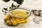 Oliven neben einer Schale mit Olivenöl